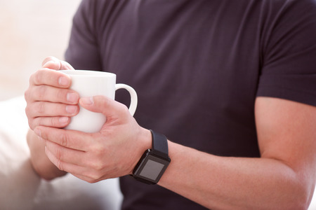 courteous: I need some coffee. Close up of hands of a man holding a cup with both hands and wearing smartwatch Stock Photo