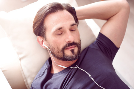 desired: Desired rest. Mature bearded man lying on the couch and sleeping while listening to music through earphones