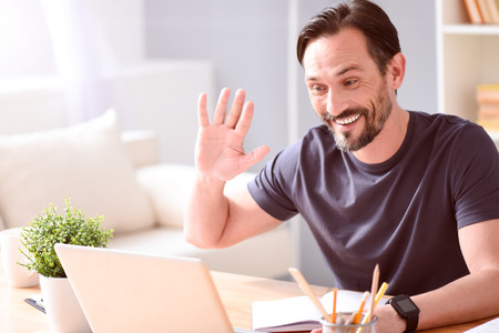 amiable: Hey you. Pleasant amiable mature man chatting on the laptop while sitting at the table at home