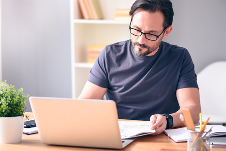 rigor: Analyzing the situation. Serious mature bearded man with glasses looking at newspaper while sitting in front of the laptop at the table
