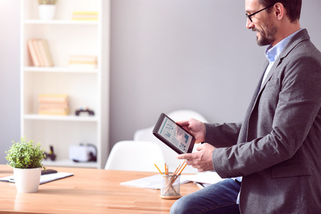 rigor: Lets have it done. Elegant bearded mature man with glasses sitting on the table and looking at the tablet with a chart Stock Photo