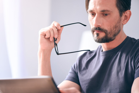 rigor: Feeling sad. Gloomy serious mature bearded man holding glasses in his hand while looking at the screen of laptop and sitting at the table