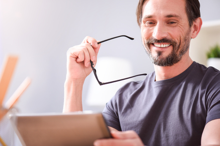 sincerely: I am so happy. Joyful bearded middle aged man smiling sincerely and holding glasses while sitting and looking at the tablet in his hands Stock Photo
