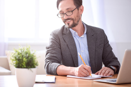 contented: Feeling confident. Contented middle aged man with glasses writing in his notebook and looking at the papers Stock Photo