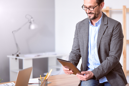 rigor: Good job. Handsome mature entrepreneur with glasses smiling while holding a tablet and sitting on the table