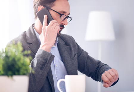 respectful: Fixing a meeting. Respectful bearded man with glasses looking at his smart watch while talking on the phone
