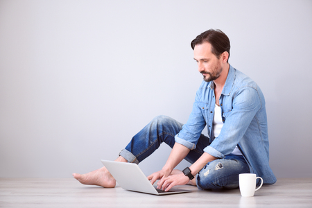 liable: Some reflection. Pensive mature bearded man working on the laptop while sitting on the floor on the grey background