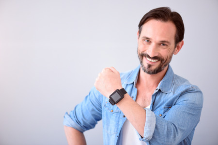 affable: Look here. Confident smiling mature man showing a smart watch on his wrist while standing on the grey background