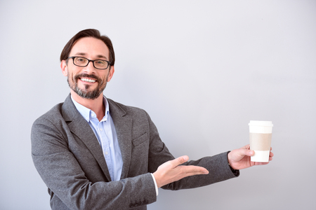 respectable: So delicious. Respectable middle aged man pointing with one hand at a cup of coffee while standing isolated on the grey background