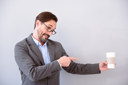 affable: Strongly advise you. Pleasant respectable middle aged man pointing with his finger at a cup of coffee while standing isolated on the grey background