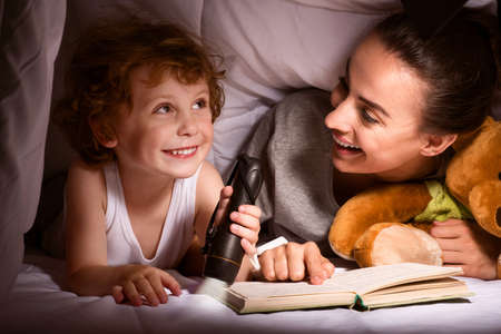 adult's: Our kingdom. Cheerful young mother and cute child with flashlight reading a book under the blanket