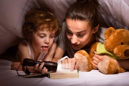 Cuento antes de dormir. madre moderna joven que lee un cuento a su hijo con una linterna en una cabaña de mantas Foto de archivo