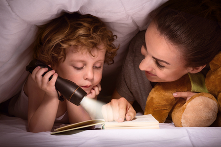 I like my mum. Lovely young mother reading a book to her tired little son after making a hut of blankets on the bed Stockfoto