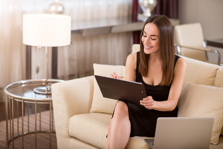 proficient: Nice work. Happy beautiful young woman looking down and taking notes while sitting on the sofa near an open laptop