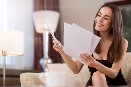 proficient: Lets have a look. Adorable delighted professional smiling and examining documents while sitting on the couch