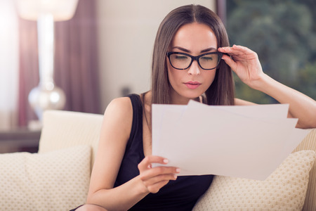 liable: Involved in work. Pensive gorgeous young woman touching glasses while analyzing attentively documents and sitting on the sofa Stock Photo