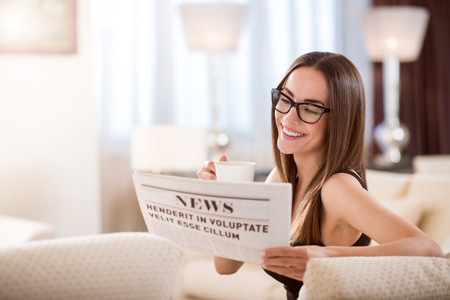 waiting glance: What is new. Amazing relaxed smiling woman sitting on the couch with a cup and reading newspaper Stock Photo