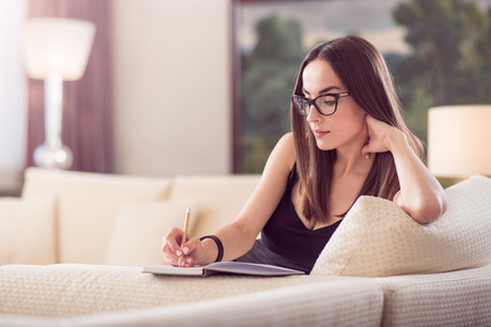rigor: Calm time. Thoughtful relaxed adorable woman sitting on the sofa and writing in the notebook and touching a neck with her hand