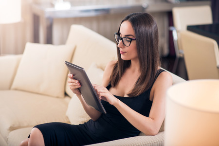 Lets look at it. Clever young woman with glasses sitting on the couch and using a tablet choosing something