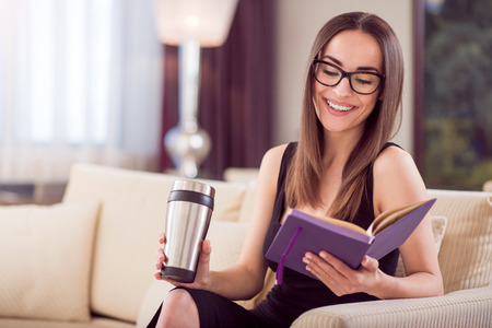 Well organized. Contented young adorable woman sitting on the sofa and looking at her diary while holding a thermo mug