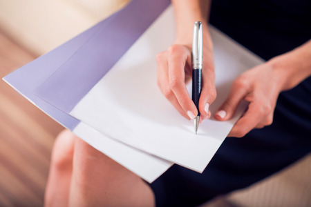 proficient: Lets do it. Close up of hands of a woman writing on the beautiful sheet of paper while sitting
