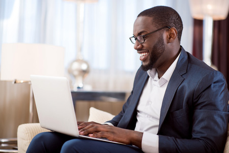liable: Pleasant work. Profile of an afro American businessman working on the laptop while sitting on the sofa in the hotel