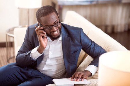 contented: Fixing a meeting. Contented confident mature afro American professional talking on the phone and checking information in his notebook Stock Photo