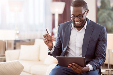 contented: So easy. Contented handsome afro American man holding a bank card and looking at the screen of a tablet while sitting