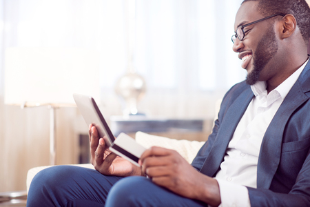 contented: Lets see. Profile of a mature contented afro American man in suit holding a bank card while looking at the tablet and sitting on the couch