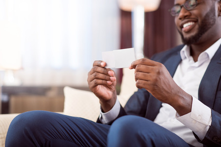 glad: My contact information. Glad successful afro American man holding a blank white business card while sitting Stock Photo