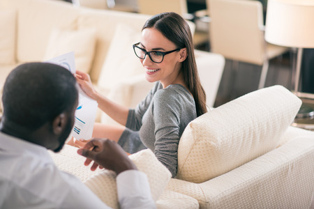 contended: You are right. Gorgeous young woman looking at her colleague while holding sheets of paper with diagrams and sitting on the sofa Stock Photo