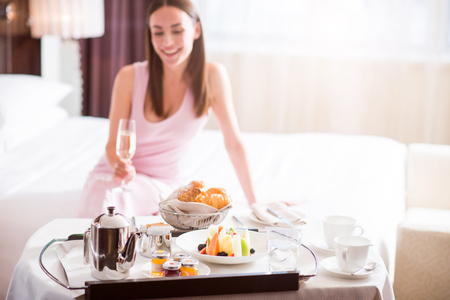 excellent service: Excellent service. Close up of a tray with a breakfast with a beautiful woman drinking champagne on the background Stock Photo