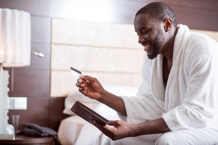 contented: It is comfortable. Contented handsome afro American man wearing a bathrobe holding a bank card and looking at the screen of a tablet while sitting on the bed in a hotel