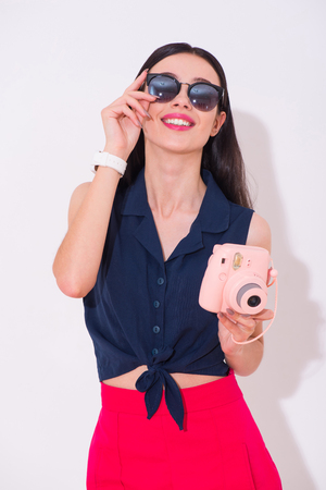 expressing joy: Live bright. Cheerful delighted smiling woman holding photo camera and expressing joy while standing isolated on white background