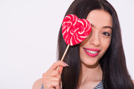 expressing joy: Sweeten your life. Portrait of cheerful pleasant woman holding lollypop and smiling while expressing joy