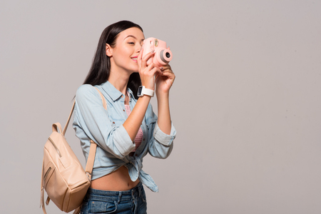 gladness: Say cheese. Positive delighted smiling woman holding photo camera and making shots while expressing gladness Stock Photo