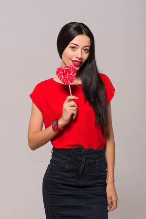 brighten: Brighten your life. Cheerful charming woman holding lollypop and smiling while standing isolated on grey background Stock Photo