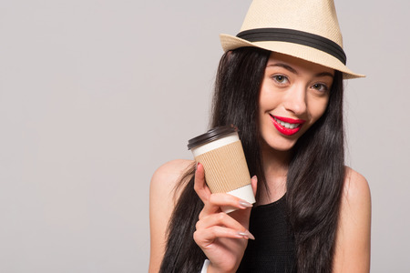 gladness: Magic beverage. Pleasant beautiful joyful woman holding coffee and going to drink it while expressing gladness Stock Photo