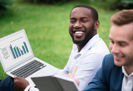 delighted: Evince your emotions. Cheerful delighted handsome smiling man sitting on the grass and holding laptop while resting with his colleague