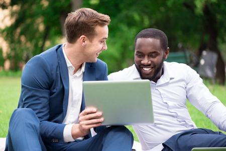 expressing joy: Just look. Overjoyed smiling content colleagues sitting on the grass and expressing joy while using laptop Stock Photo