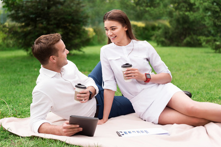 pleasant: Make a pause. Pleasant cheerful smiling colleagues drinking coffee and resting while sitting on the grass