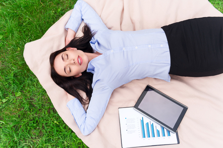 relieve: Relieve stress. Top view of delighted beautiful smiling woman lying on the blanket and closing her eyes while resting after work Stock Photo