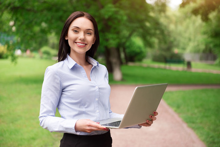 gladness: Modern user. Positive smiling beautiful woman expressing gladness and using laptop while standing outdoor Stock Photo