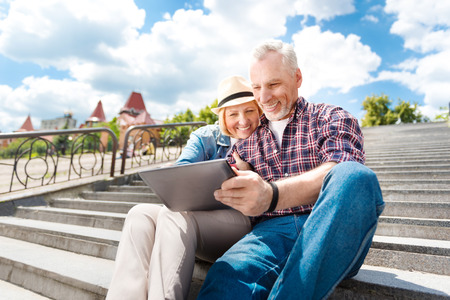 grandkids: Beloved couple. Cheerful and merry senior couple laughing while using their digital tablet to video chat with their grandkids while being outdoors and sitting on the stairs Stock Photo