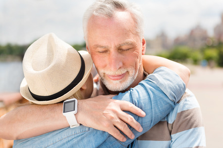 tenderness: You complete me. Close up of smiling and happy aged couple embracing each other and enjoying time together feeling love and tenderness