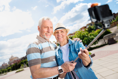 Honey. Smiling and positive elderly couple relaxing together being outdoors and making selfies while using a smartphone and a selfie stick Reklamní fotografie