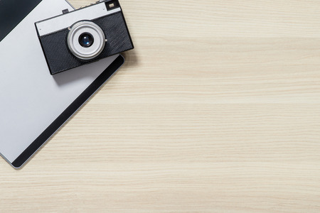 wood surface: Ready to make shots. Top view of photo camera lying on the table
