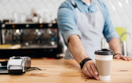nourishing: Nourishing coffee. Cropped image of young male barista giving a paper cup of coffee at coffeehouse