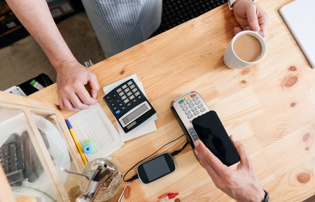 technology transaction: Transaction. Cropped image, top view of man paying with NFC technology on mobile phone being in coffeehouse Stock Photo
