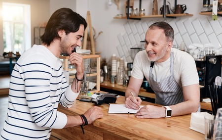 noting: Noting order. Young happy and merry man making an order while standing near bar and positive male barista making notes